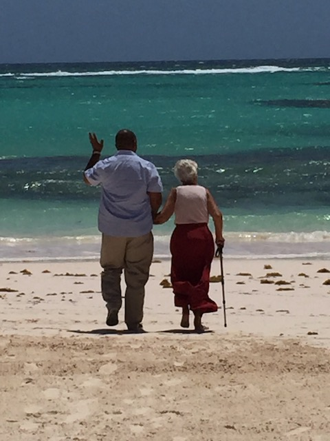 My lovely Mum being walked down the beach to have a paddle in the sea - courtesy of the very gallant Ricardo Knowles......